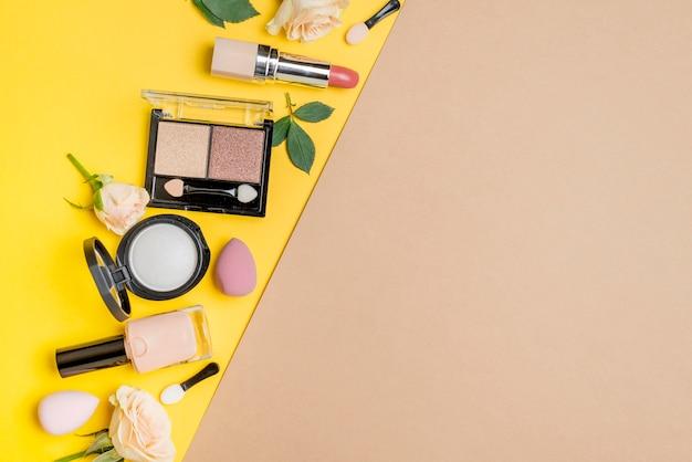 二色の背景にコピースペースを持つさまざまな化粧品の品揃え
