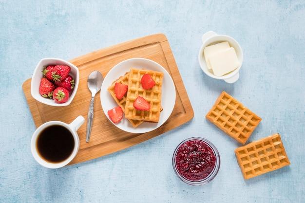 Доска с вафлями и фруктами на столе