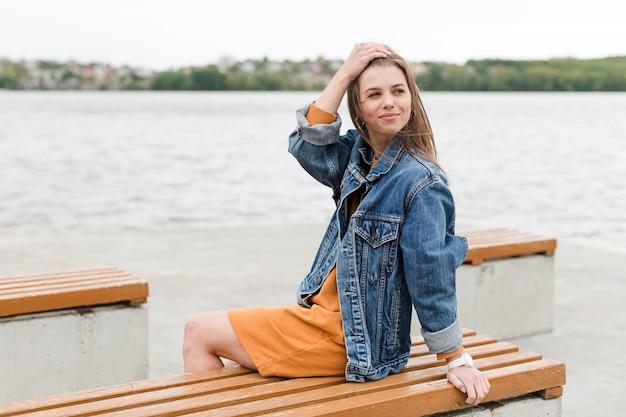 海辺でベンチに座っている女性