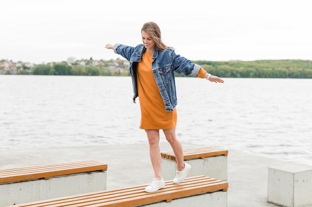 海のベンチの上を歩く女性