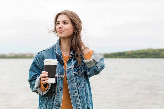 海辺でコーヒーを持つ女性