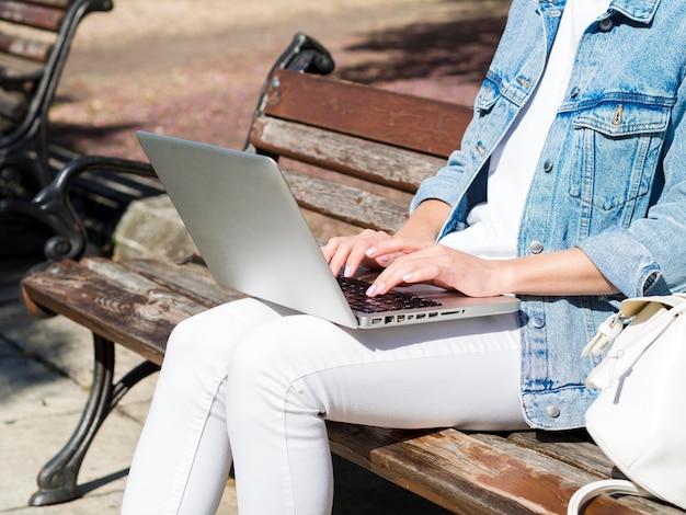 Вид сбоку женщины на скамейке, работает на ноутбуке