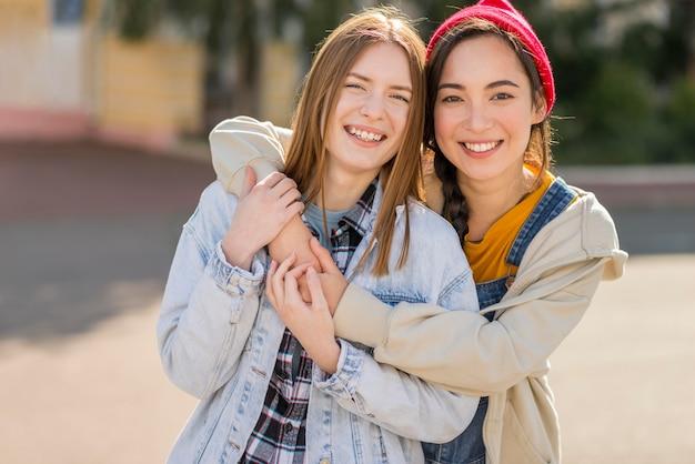 Улыбающиеся подружки обнимаются