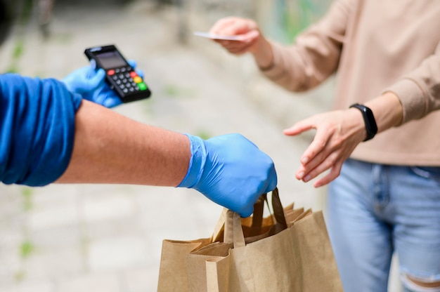 Крупным планом женщина платит за заказанные продукты