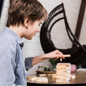 ジェンガを自宅で遊ぶ少年