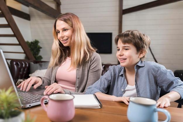 Красивая мама работает рядом с сыном