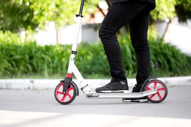 Бизнесмен езда скутер на открытом воздухе