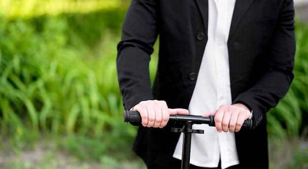 Элегантный бизнесмен езда скутер на открытом воздухе