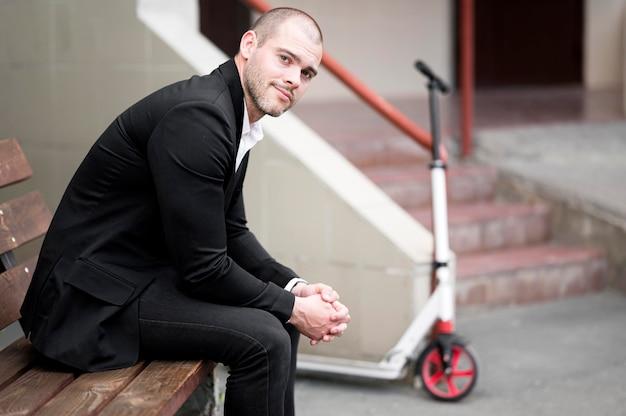 Красивый бизнесмен сидит на скамейке