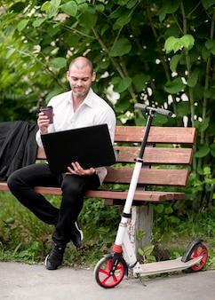 Взрослый бизнесмен, сидя на скамейке на открытом воздухе