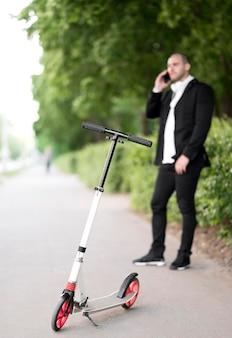 電話で話している実業家とスクーター