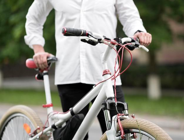 Элегантный взрослый мужчина держит современный велосипед
