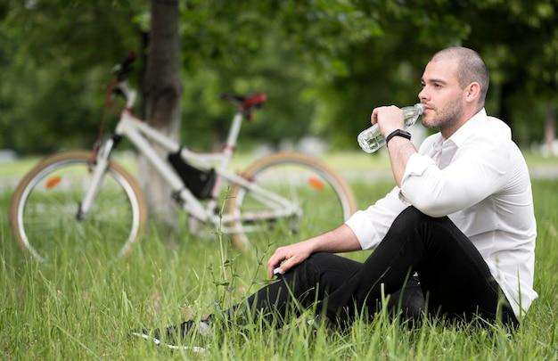 Красивый взрослый мужчина питьевой воды на открытом воздухе