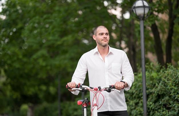 Портрет взрослого мужчины с велосипедом на открытом воздухе