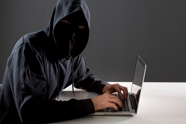 ラップトップを持つ男性のハッカーの側面図