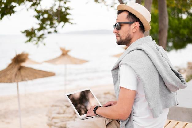 ラップトップに取り組んでビーチでサングラスを持つ男の側面図