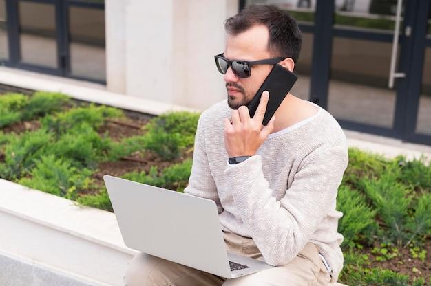ノートパソコンとスマートフォンの屋外での作業を持つ男