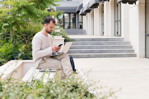 ノートパソコンで作業する外の男の側面図