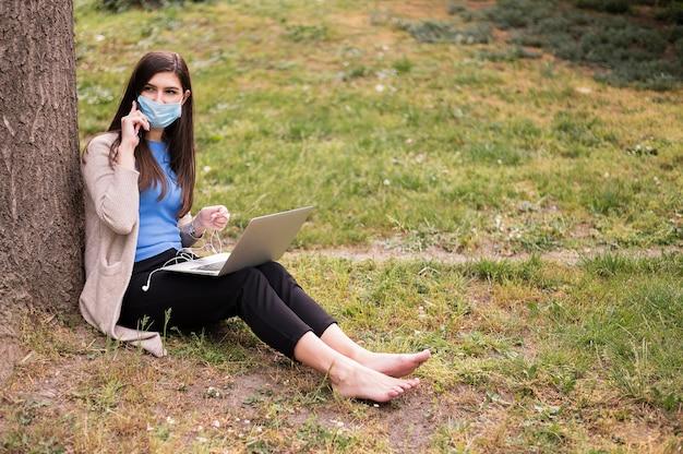 屋外のラップトップに取り組んで医療マスクを持つ女性