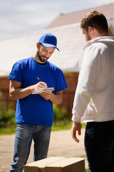 配送書類に署名する若い配達人