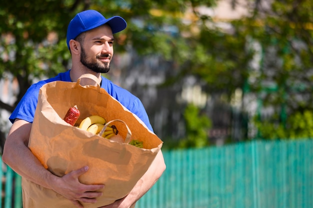 Портрет доставщика, несущего продуктовую сумку