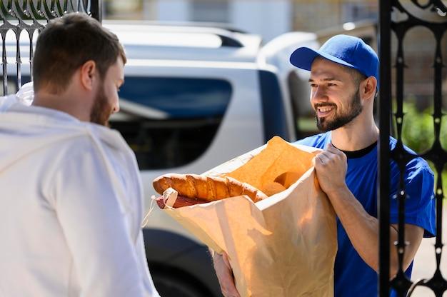 若い男が食料品を顧客に提供して満足