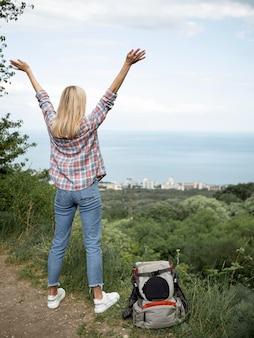 山の頂上に到達する幸せな女性