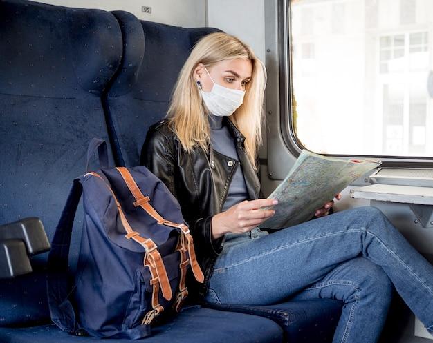 Женщина в поезде, консультирующаяся с картой