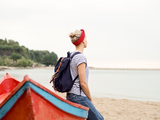 海辺でボートに座っているサイドビュー女性