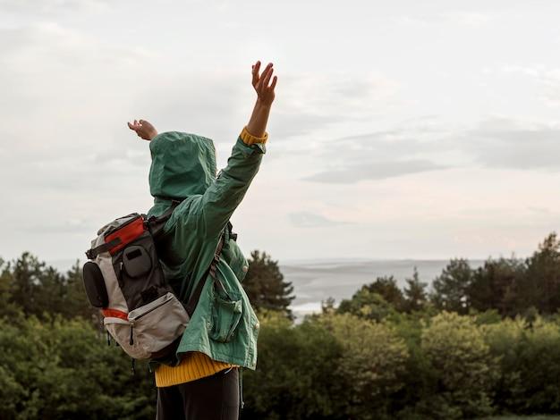 サイドビューのバックパックを持つ若い女性