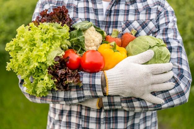 Крупным планом мужчина держит овощи