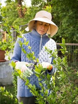 彼女の庭から葉を切る女性