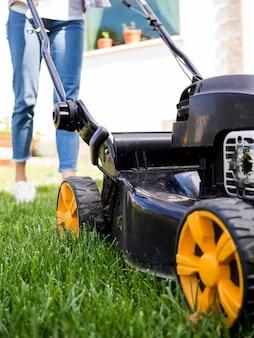庭のクローズアップを刈る女性