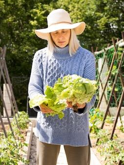 新鮮な緑のキャベツを保持しているブロンドの女性