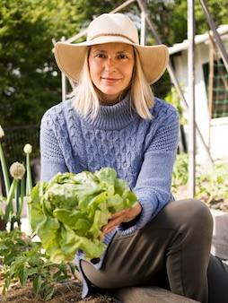 緑のキャベツを保持している正面図女性