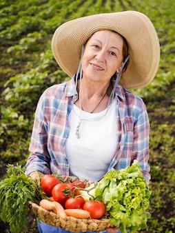 Женщина вид спереди держит корзину, полную овощей