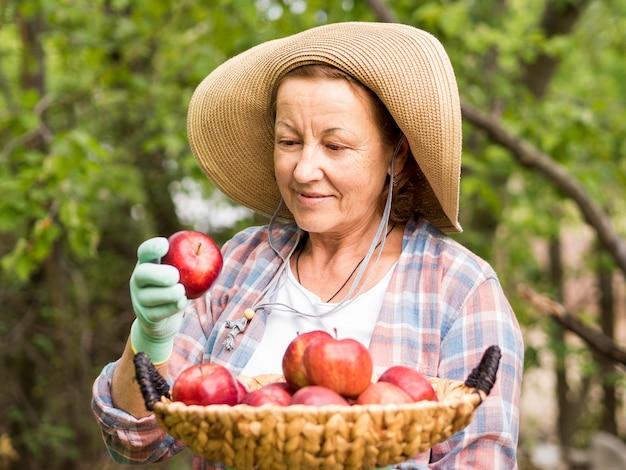 Женщина вид спереди держит корзину, полную яблок