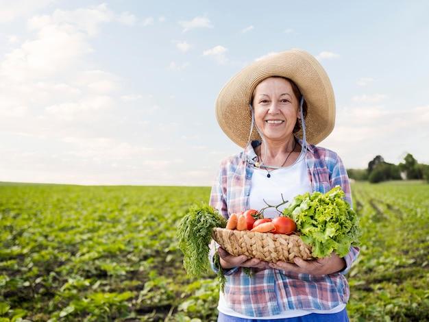 Женщина держит корзину, полную овощей