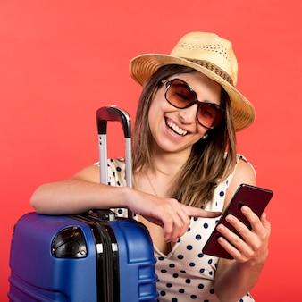 携帯電話でミディアムショットのスマイリー女性