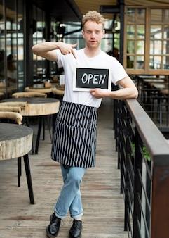 オープンサインを保持しているエプロンの男性ウェイター