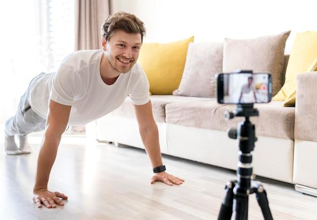 ハンサムな男性が自宅でパーソナルトレーニングを記録
