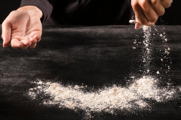 小麦粉を注ぐクローズアップ手