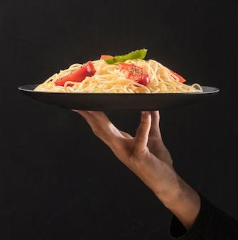 Крупным планом рука держит тарелку с макаронами