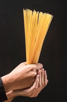 Макро руки держат макароны