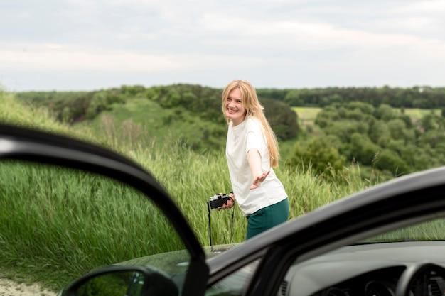 カメラを押しながら車の前でポーズの女性