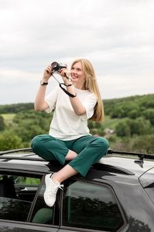 車に立っている間自然の写真を撮る女性