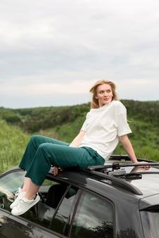 Женщина позирует на природе, стоя на вершине автомобиля