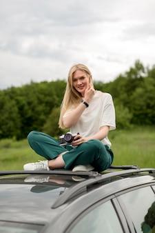 車の上でポーズをとって魅力的な女性