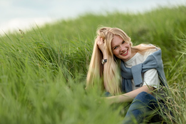 スマイリー女性が草を介してポーズ