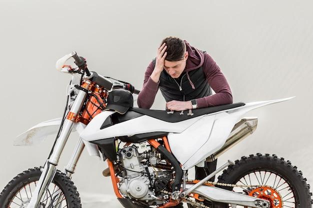 壊れたバイクを心配している男性の正面図